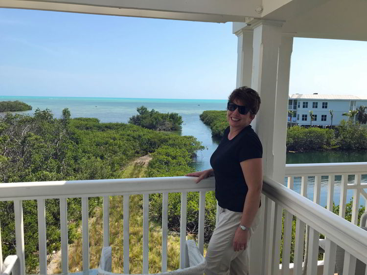 An image of a woman standing on a balcony at Oceans Edge Resort and Marina in Key West, Florida.