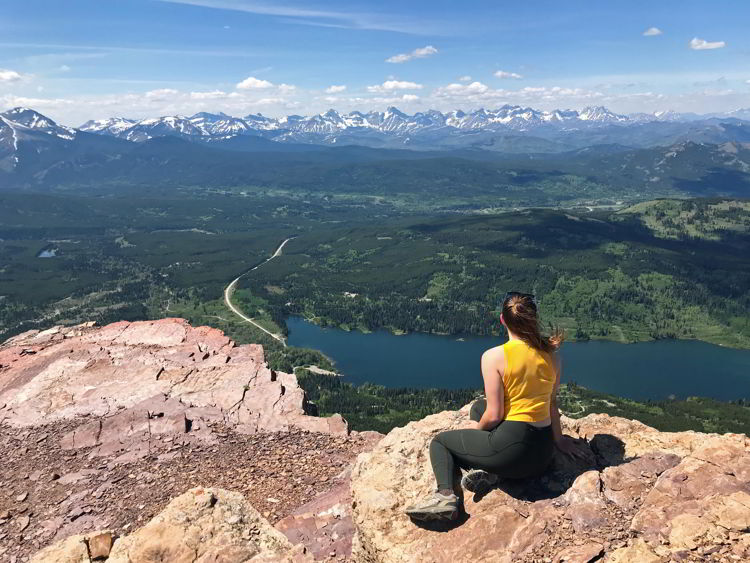 An image of a young woman taking in the view from the top of Table Mountain, Alberta.