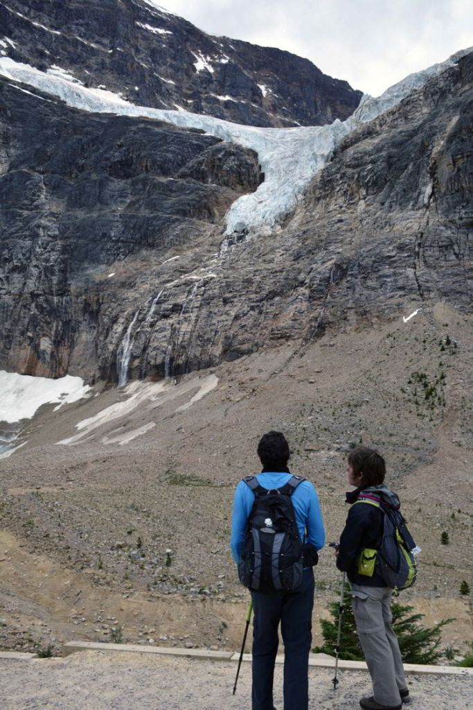 An image of two people looking up at the Angel Glacier on the Mount Edith Cavell trail in Jasper National Park - Jasper hikes.