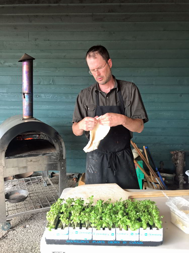 An image of a man making pizza at Broxburn Vegetables and Cafe in Lethbridge, Alberta.