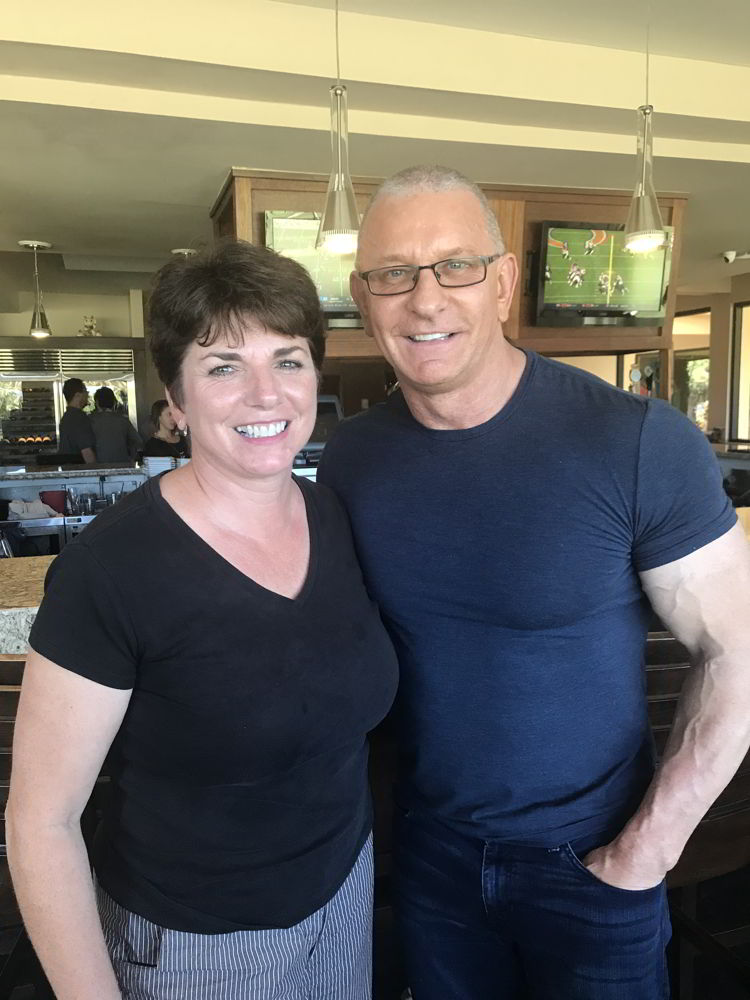 An image of a woman standing next to Robert Irvine at the Hawaii Food and Wine Festival in 2018.