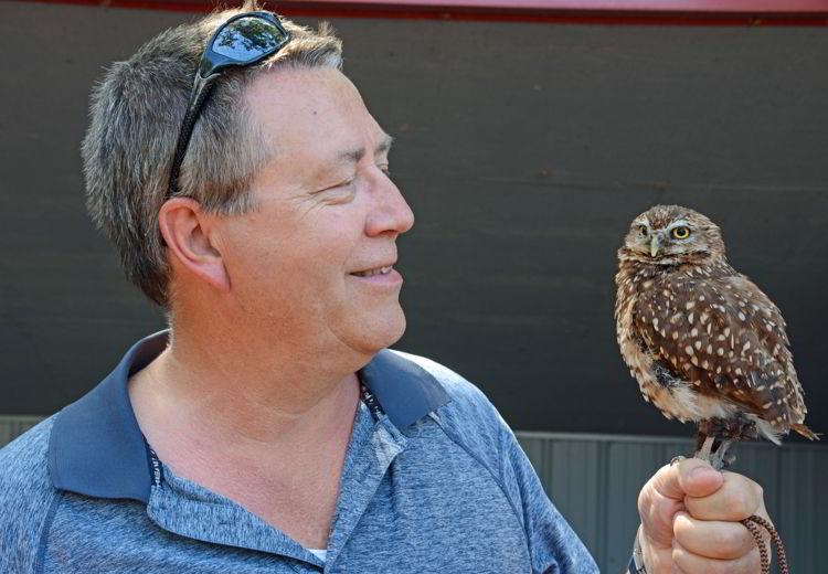 An image of a man holding a burrowing owl at the Alberta Birds of Prey Centre near Lethbridge, Alberta.