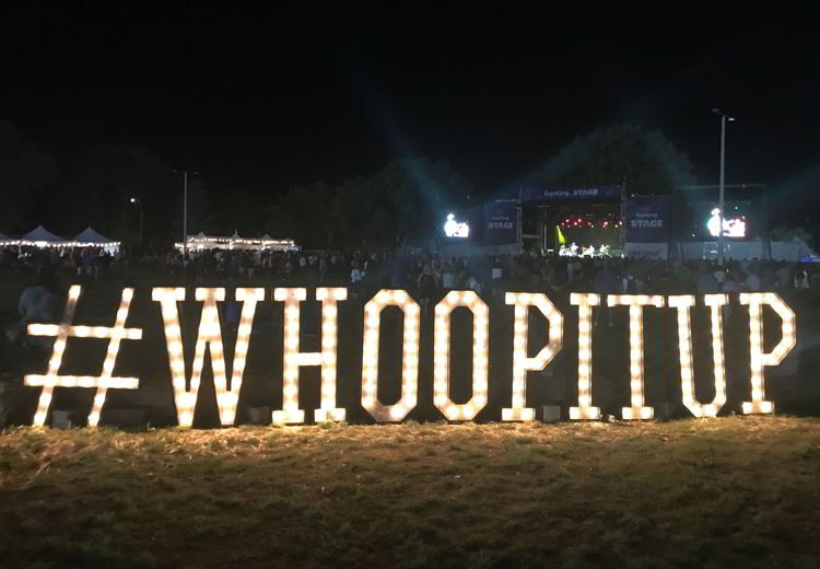 An image of the Whoop it up sign lit up at Whoop-up days in Lethbridge, Alberta.