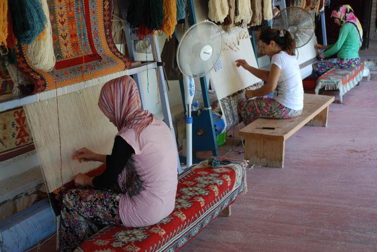 An image of women weaving rugs in Turkey.