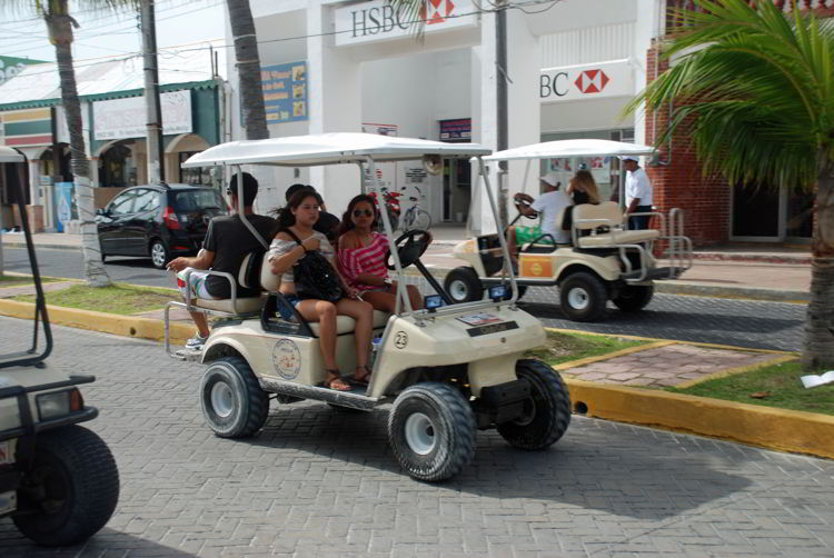 An image of people riding in a golf cart on Isla Mujeres.