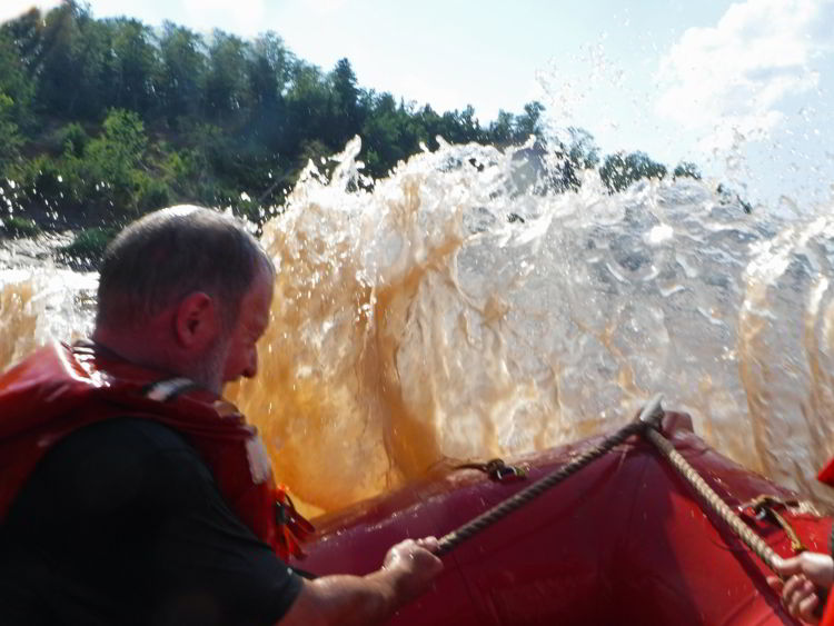 An image of muddy water coming into the zodiac boat when tidal bore rafting on the Schubenacadie River in Nova Scotia.