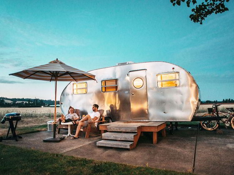 An image of two people sitting in front of a camping trailer - Ruckify - glamping in Alberta.