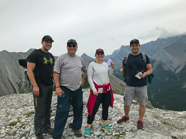 An image of four people holding the summit register on Grant MacEwan Peak near Canmore, Alberta.