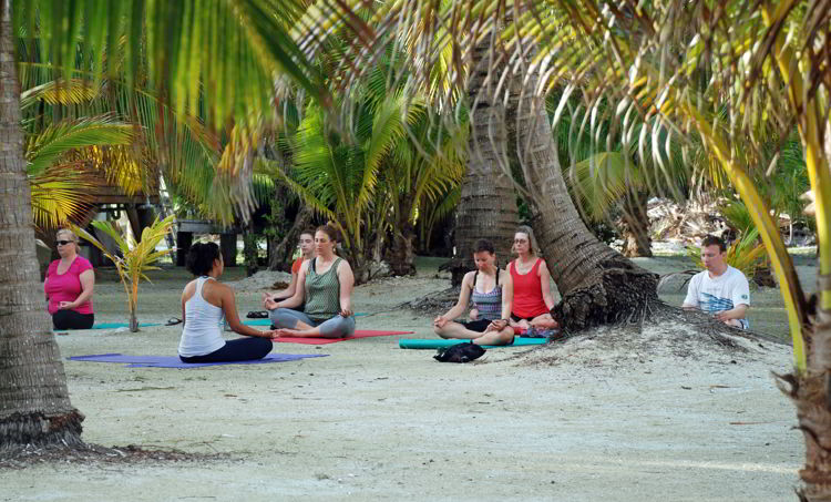 An image of a group of people doing a meditation exercise on a beach. - yoga retreat costa rica