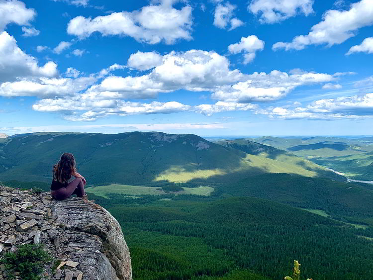 An image of a woman taking in the view at the top of Nihahi Ridge in Kananaskis, Alberta, Canada.