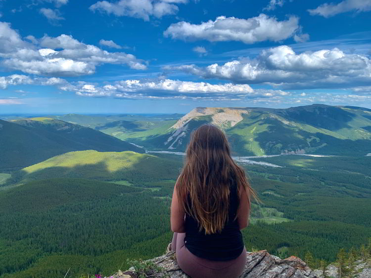 An image of a woman sitting at the top of Nihahi Ridge in Kananaskis Country in Alberta, Canada.