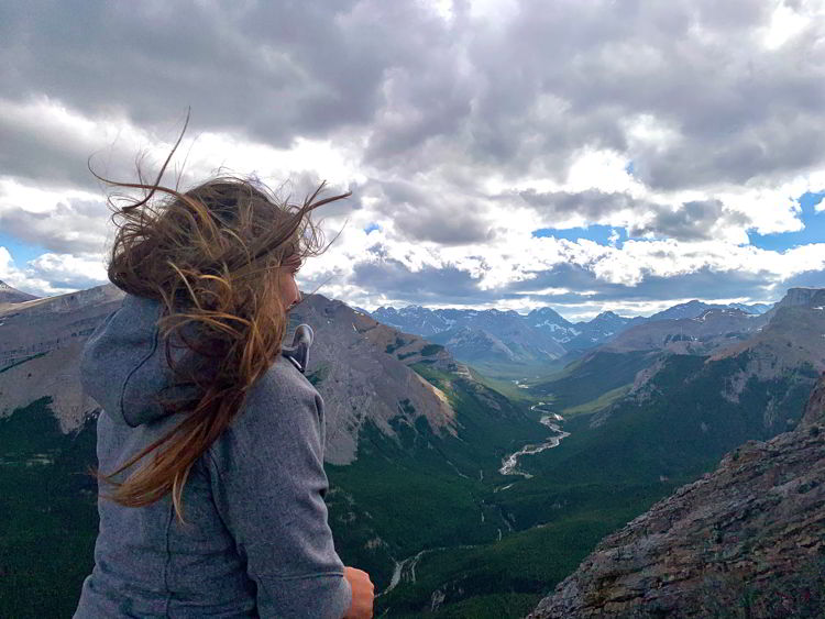 An image of a woman with her long hair blowing in the wind on Nahini Ridge in Kananaskis Country in Alberta, Canada.