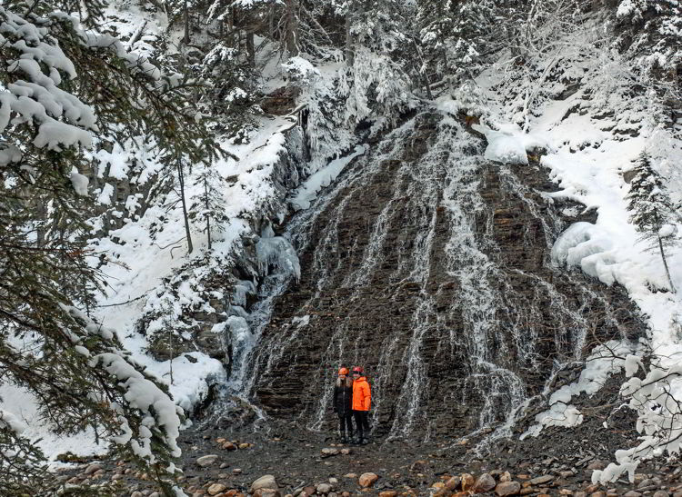An image of a couple standing in front of a waterfall in Maligne Canyon in winter.
