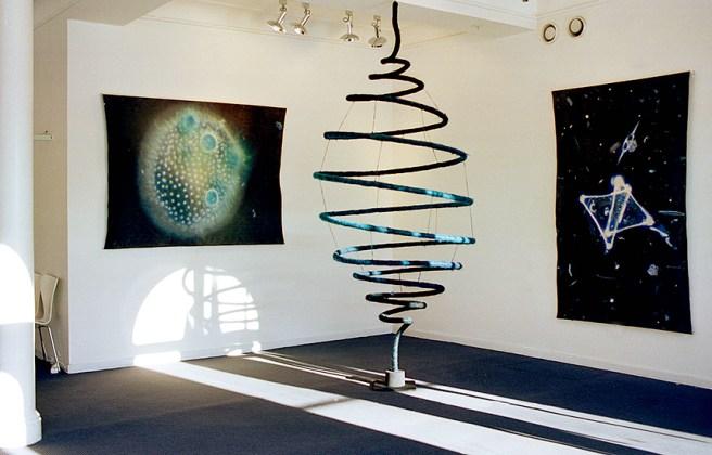 Vindel, textil skulptur i tovad ull som roterar med ett varv/minut. På väggen hänger två fotografier tryckta på tovad ull. ©Maria Wangi Ibohm, Maria Backström