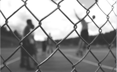 Students playing basketball behind a chain linked fence.