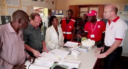 Klaas Proesmans (r) in Rode Kruis kleding + polsbandje in de kliniek in Oeganda  Screenshot video: BEWIJS ! Rode Kruis genas 154 malariapatiënten met MMS (8)