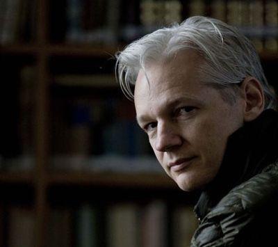 Julian Assange van Wikileaks met het resultaat van al zijn inspanningen: krantenkoppen met nieuws dat verborgen diende te blijven..