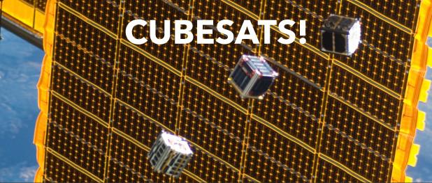 Satellietjes met een inhoud van 1 liter en gewicht van 1,5 kg in vergelijking met het formaat van de grote satellieten, waarvan je op de achtergrond een uitgeklapt zonnepaneel ziet.
