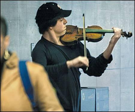 De jonge straatmuzikant bij de ingang van het metrostation.