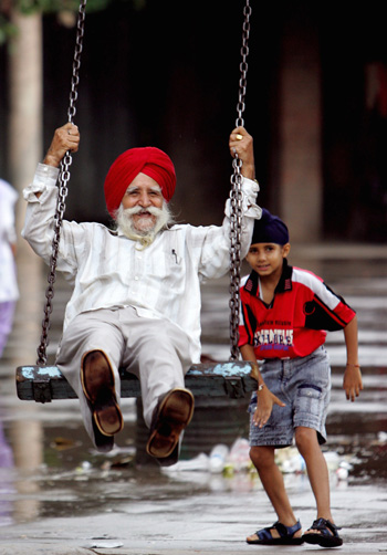 A Sikh child pushes his grandfather on a swing in a park in the northern Indian city Chandigarh