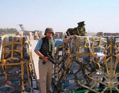 Een soldaat bij een van de pallets met 100 dollarbiljetten.
