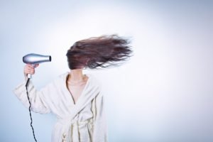 a woman with long hair blowing her hair with hairdryer