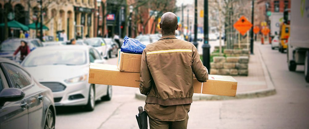 ecommerce logistics - delivery man walking down street with packages to in hand