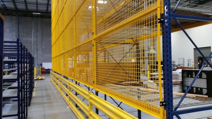 Warehouse shelving outfitted with bright yellow wire grids on the bottoms and back to protect the floors