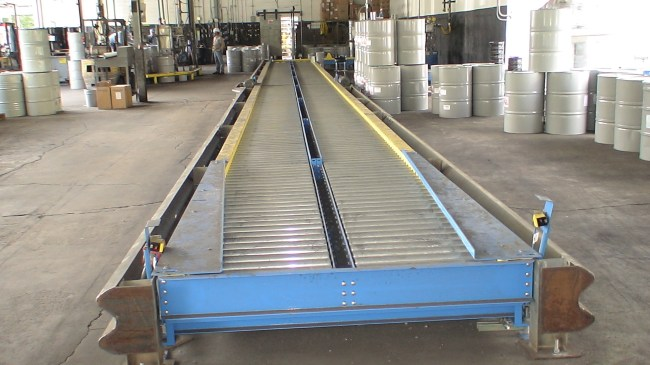 A conveyor belt stands empty with metal drums stacked around it.