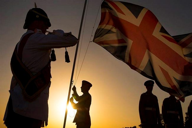 Personnel from Episkopi Garrison in Cyprus lowering the Union Jack on the Episkopi cliffs as part of Remembrance Day events