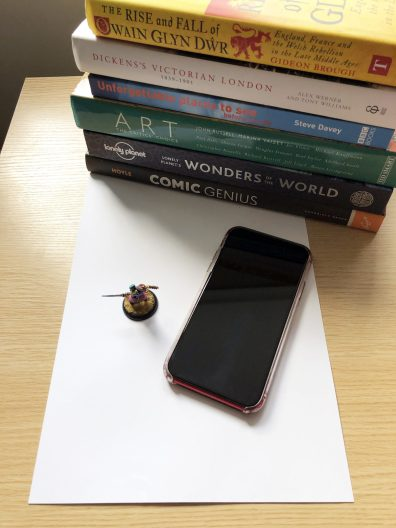 Everything you need: A backdrop (sheets of paper). Some books (to support the backdrop). A phone (to take the photos). A figure (to star in the photo).