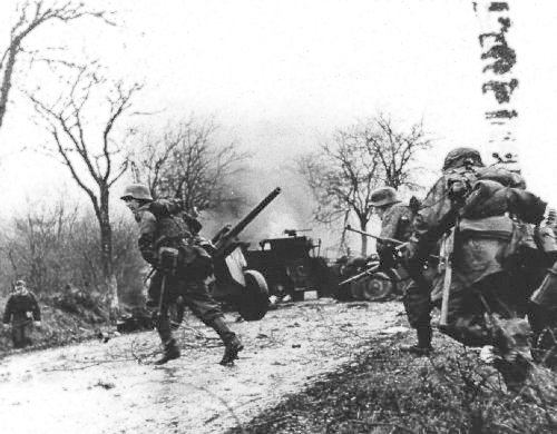 German troops advancing past American equipment at the Battle of the Bulge via commons.wikimedia.org