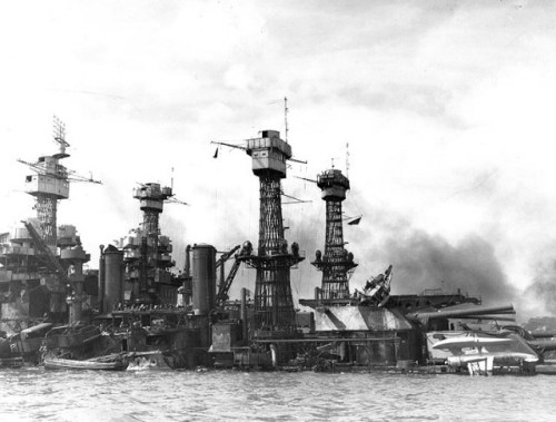 "The sunken battleship USS West Virginia (BB-48) at Pearl Harbor after her fires were out, possibly on 8 December 1941. USS Tennessee (BB-43) is inboard. A Vought OS2U Kingfisher floatplane (marked ""4-O-3"") is upside down on West Virginia's main deck. A second OS2U is partially burned out atop the Turret No. 3 catapult. Note the CXAM radar antenna atop West Virginia´s foremast."
