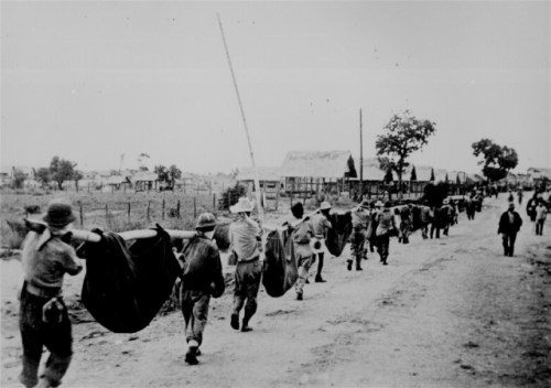 """This picture, captured from the Japanese, shows American prisoners using improvised litters to carry those of their comrades who, from the lack of food or water on the march from Bataan, fell along the road."" Philippines, May 1942. 208-AA-288BB-2. (ww2_131.jpg) ""At the time of its release, this photo was identified as dead and wounded being carried by fellow prisoners during the Bataan Death March in April 1942 ... Subsequent information from military archivists, the National Archives and Records Administration, and surviving prisoners, strongly suggests that this photo may actually depict a burial detail at Camp O'Donnell."