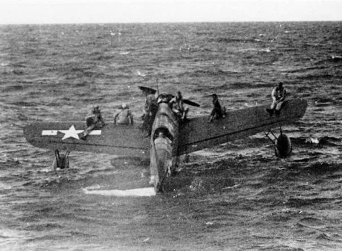 Downed American airmen near Truk Lagoon are ferried by a Vought OS2U Kingfisher to USS Tang.