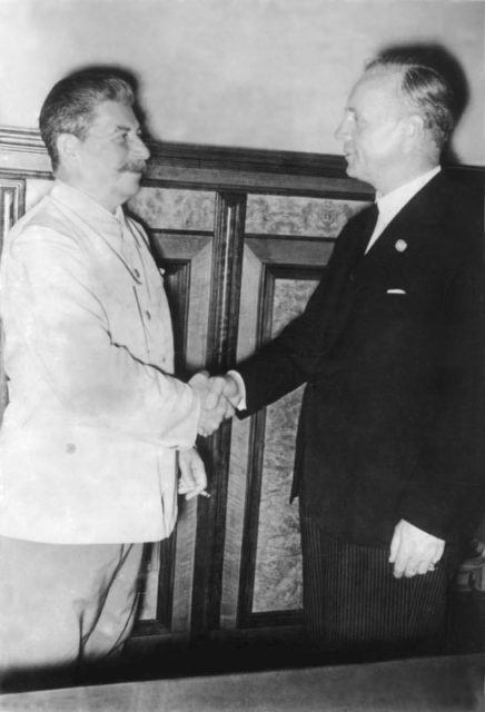 Soviet Premier Joseph Stalin and German foreign minister Joachim von Ribbentrop shaking hands over the Nazi-Soviet Pact (also known as the Molotov-Ribbentrop Pact) on August 23, 1939 Image Source: Bundesarchiv, Bild 183-H27337 / CC-BY-SA 3.0