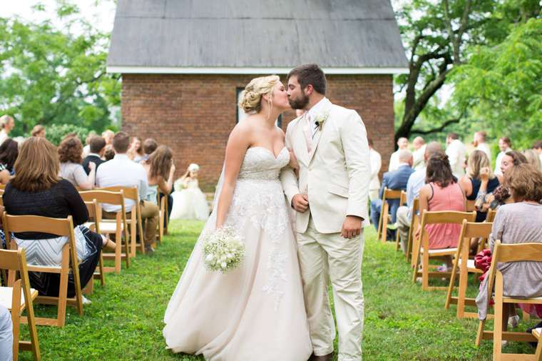 Couple kiss as they exit their preppy southern chic outdoor ceremony