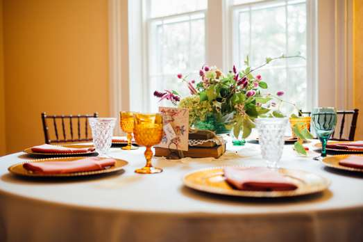 Heirloom table setting with gold chargers and coral napkins