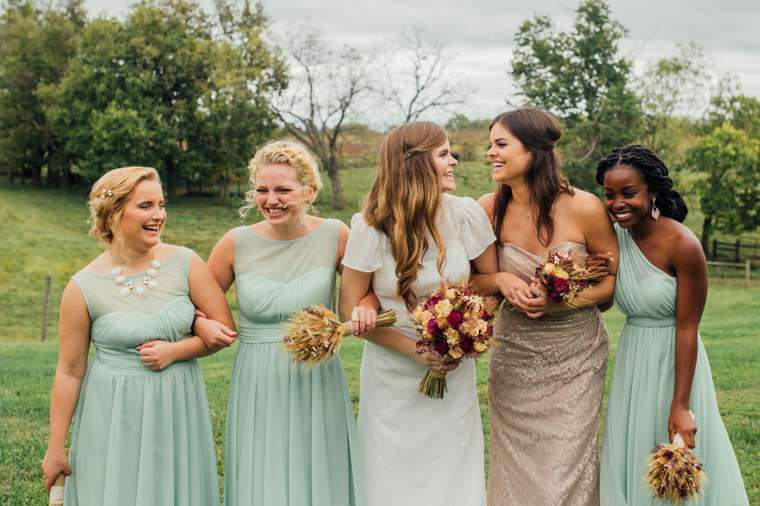 Informal bridal party photo from farm wedding with fall floral bouqets