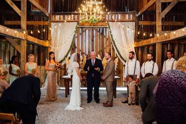 Wedding party standing for charming wedding ceremony in a rustic barn