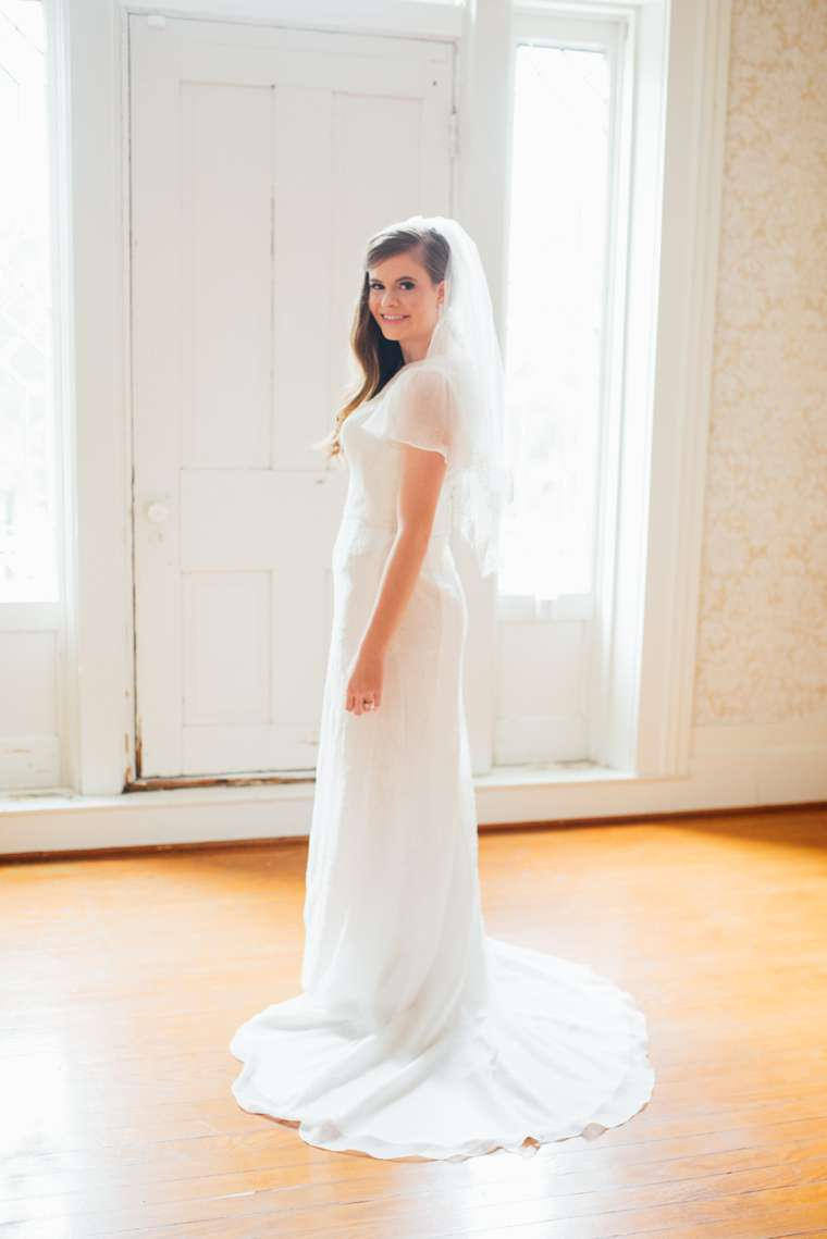 Bride in classic and conservative capsleeve bridal gown with veil