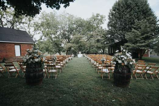 Outdoor rustic country wedding ceremony in the back yard at Warrenwood Manor with bourbon barrels