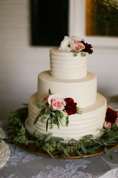 Three-tier textured ivory wedding cake with eucalyptus and roses