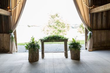 Wedding alter with rustic table, tree stumps and greenery arrangements at barn wedding