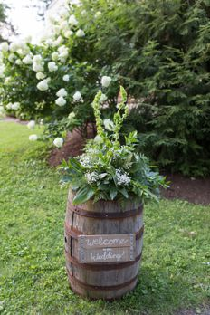 Bourbon barrel with greenery arrangement and welcome sign