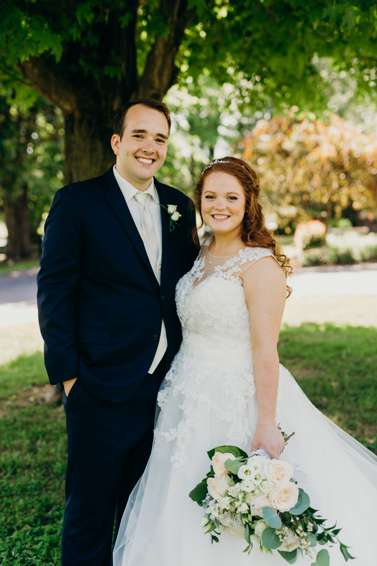 Bride in ball gown with illusion neck with half-up curly hair, groom in navy suit
