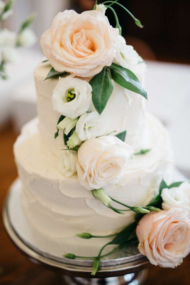 Two-tier ivory wedding cake with pale pink and ivory flowers