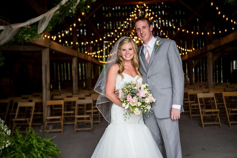 Sweet and vibrant summer wedding at Warrenwood Manor, bride & groom portrait in barn with chandeliers