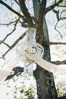 Creative ceremony backdrop | Chandelier hanging in tree with drapery