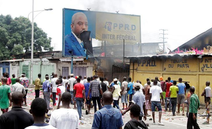 Congolese opposition supporters chant slogans as they destroy the billboard of President Joseph Kabila during a march to press the President to step down in the DRC's capital Kinshasa